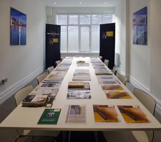 The venue with large boardroom table laid out with the submitted projects.
